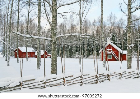 Swedish winter landscape with traditional red wooden houses covered by snow. - stock photo