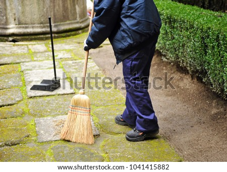 Sweeper, municipal cleaning worker sweeping autumn leaves in the garden