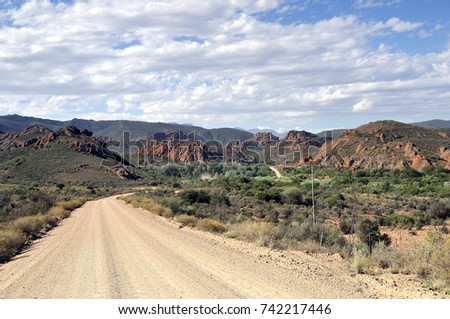 Sweeping dirt road leading to hills under cloudy blue skies