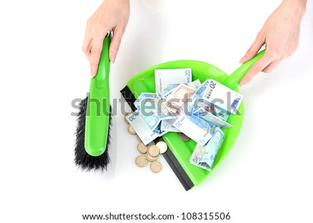 Sweeps money in the shovel on white background close-up - stock photo