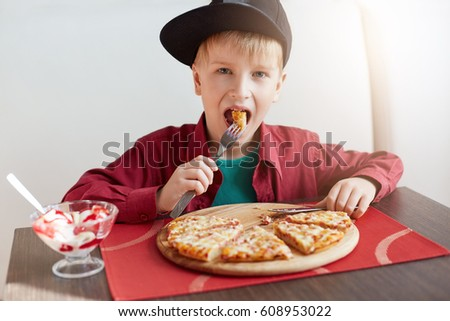 Sweet adorable child, boy in stylish cap and red shirt eating pizza and ice-cream at a restaurant. Fashion little boy having breakfast at cafe. People and lifestyle concept.