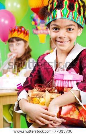 Sweet african- american girl holding presents, her guests sit behind - stock photo