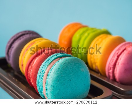 Sweet and colorful french macarons or macaroons in row with blue paste colour background.