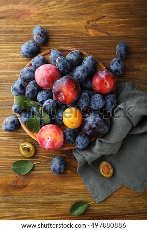 Sweet and ripe plums on wood, food top view