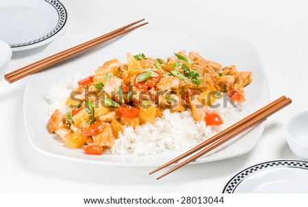 Sweet and sour chicken stir-fry on rice, with dinner settings for two - stock photo