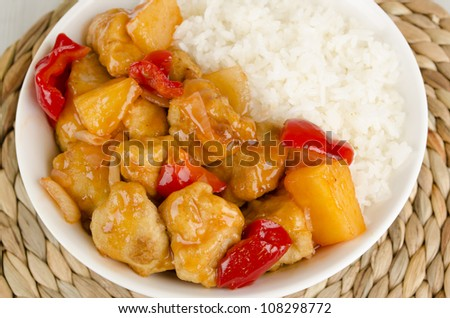 Sweet and Sour Chicken with pineapple and red bell peppers served with steamed rice - stock photo