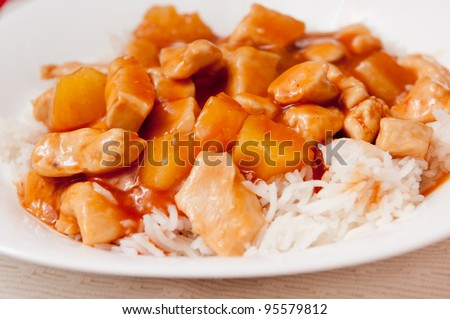 sweet and sour chicken with pineapple chunks over white rice