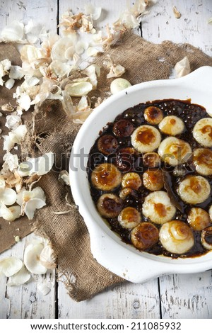 sweet and sour onions candied on balsamic vinegar on rustic background with burlap and onions peels - stock photo