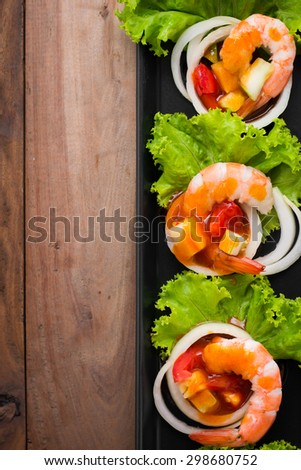 sweet and sour shrimp, prawn cocktail on long square dish and wooden table - stock photo