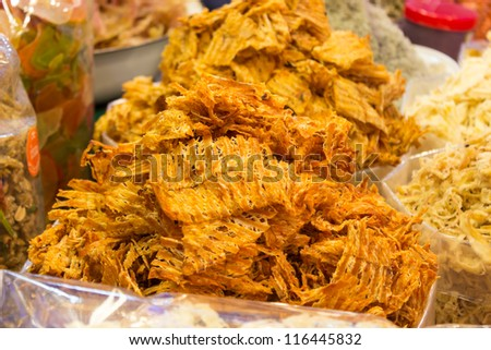 Sweet and spicy dried squid for sale at the market in Thailand. - stock photo