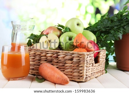 Sweet apples, juice and carrots on wooden table on natural background - stock photo