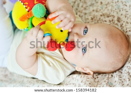 sweet baby biting a toy - stock photo