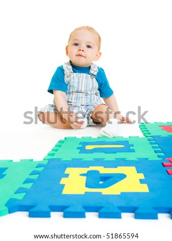 Sweet baby boy sitting behind numbers puzzle