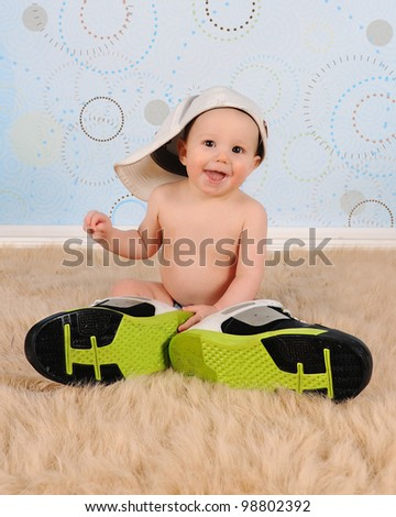 sweet baby boy sitting down wearing his Daddy's hat and sneakers - stock photo