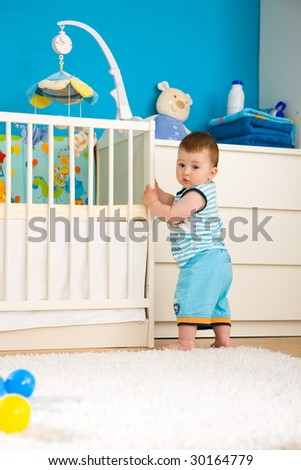 Sweet baby boy ( 1 year old ) standing at children's room in front of crib. - stock photo