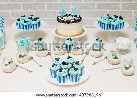 sweet baby candy buffet in blue style with a lot of decorated cakes and sweets - stock photo