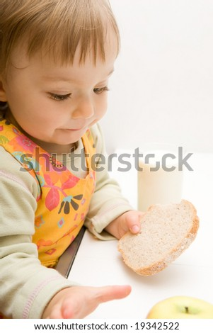 sweet baby girl eating bread - stock photo
