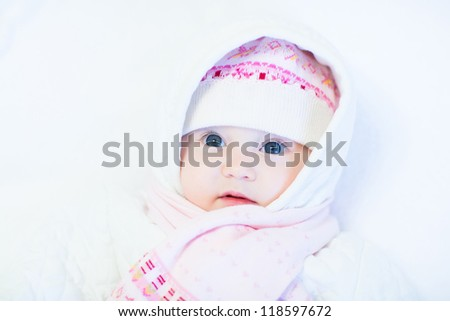 Sweet baby girl in a knitted hat and scarf on white background - stock photo