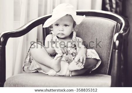 sweet baby girl sitting on the chair - stock photo