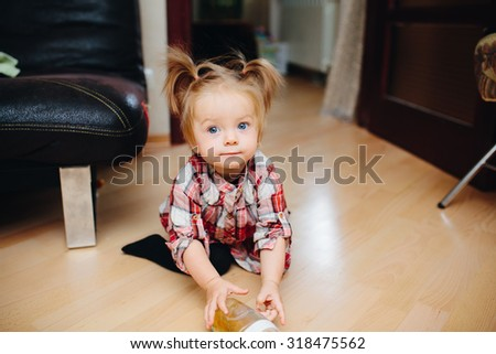 Sweet baby girl sitting on the floor and drinking tea - stock photo