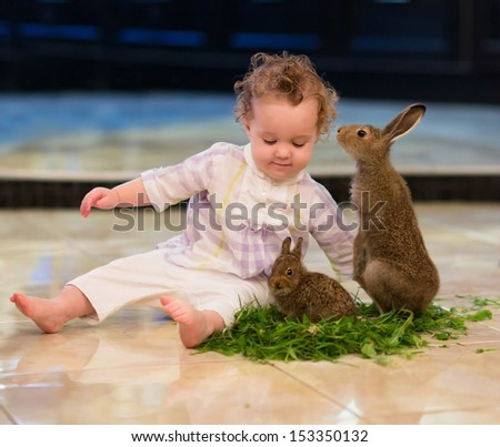 Sweet baby girl with curly hair playing with two rabbits - stock photo