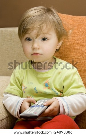 sweet baby girl with remote control on sofa - stock photo