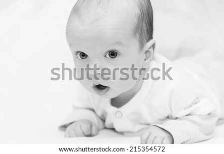 sweet baby laying on the bed on a white background  ( black and white ) - stock photo