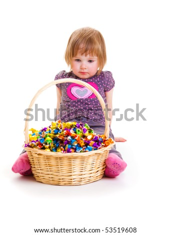 Sweet baby looking at the basket full with candies - stock photo
