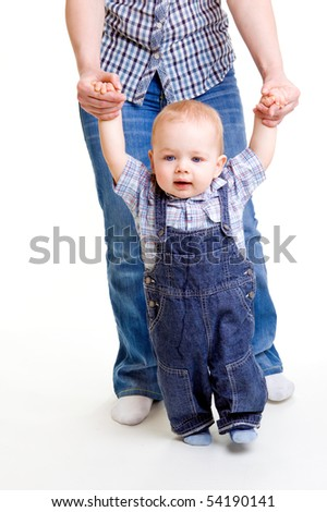 Sweet baby making first unsure steps, supported by mom - stock photo