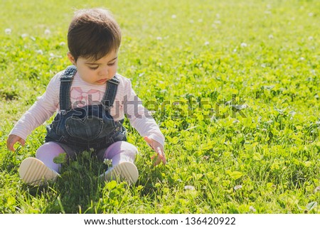 Sweet baby sit on grass with open hand