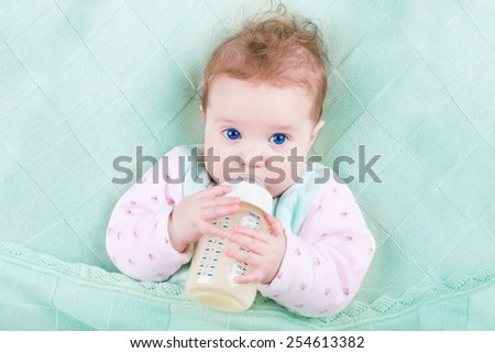 Sweet baby with big blue eyes drinking milk relaxing under a warm knitted blanket - stock photo