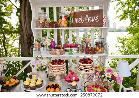 Sweet bar on summer wedding. Layer cakes with protein cream and fresh cherry and berries on a cake stand outdoors - stock photo