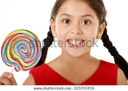 sweet beautiful latin female child holding big lollipop candy eating and licking happy and excited isolated on white background in funny crazy face expression and sugar addiction concept - stock photo