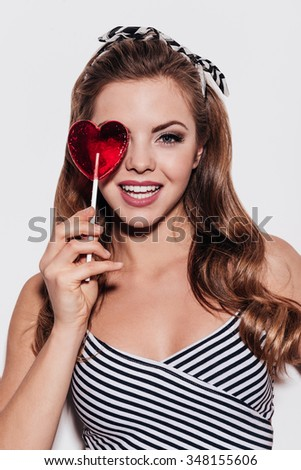Sweet beauty. Cheerful young woman looking threw a lollipop while standing against white background - stock photo