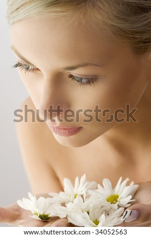 sweet beauty close up portrait of beautiful woman with some white daisy on hand - stock photo
