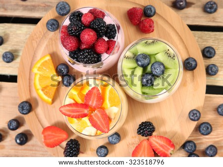sweet berries with yogurt on wooden table - stock photo