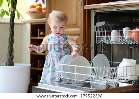 Sweet blonde toddler girl helping in the kitchen taking plates out of dish washing machine