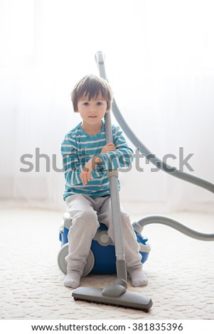 Sweet boy, playing with hoover at home, cleaning with vacuum cleaner - stock photo