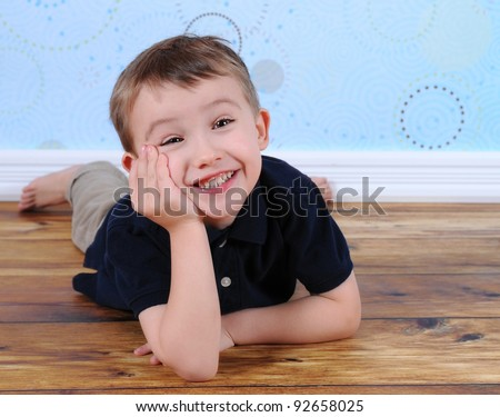 sweet boy posing with a silly grin and hand on chin. laying on floor - stock photo