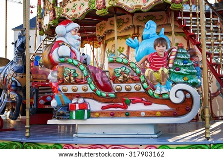 Sweet boy, riding in a Santa Claus sledge on a merry-go-round, carousel attraction in Europe, active children, summertime - stock photo