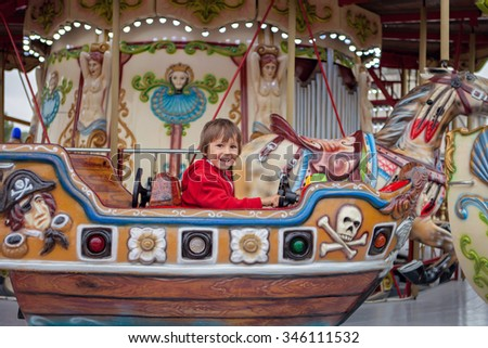 Sweet boy, riding in a train on a merry-go-round, carousel attraction in Europe, active children, summertime