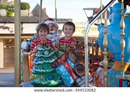 Sweet boys, brothers, riding in a Santa Claus sledge on a merry-go-round, carousel attraction in Europe, active children, summertime - stock photo