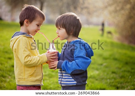 Sweet boys in the park, holding bottle with smoothie, drinking together from a straw and smiling, springtime - stock photo