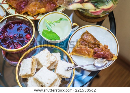 Sweet breakfast with green mint tea, homemade apple pie, jam, paste and candy. Table with ornamental cup, saucer and teapot - stock photo
