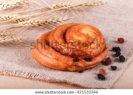 Sweet bun with raisins and vanilla cream on rustic background with spikelets. Pastries and bread in a bakery - stock photo