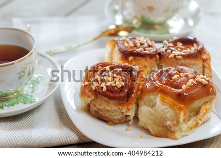 Sweet buns with cinnamon, nuts and caramel syrup. - stock photo