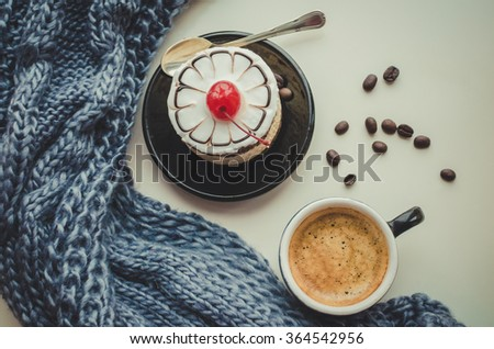 Sweet cake with a cherry, cup of coffee and coffee beans with warm knitted scarf.  Cozy winter breakfast. Good morning. Tasty food background. - stock photo