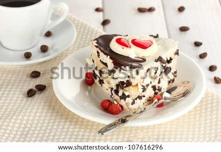 sweet cake with chocolate on plate and cup of coffee on wooden table - stock photo