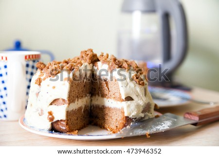 Sweet cake with cocoa and cream cheese on   table.