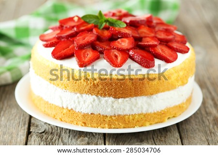Sweet cake with strawberries on plate on grey wooden background - stock photo
